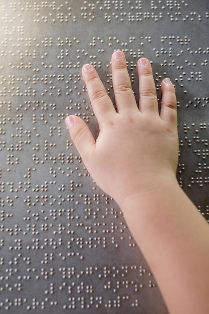A mão do garoto cego e os dedos tocando as letras em braille na placa de metal Foto Premium
