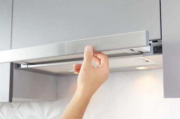 A mão do homem abre o exaustor da cozinha para cozinhar ou substituir o filtro. interior moderno em segundo plano. Foto Premium