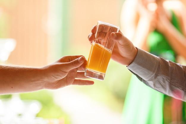 A mão do homem alcança um copo com suco fresco para outro homem Foto gratuita