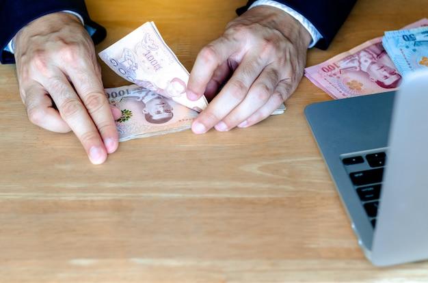 A mão do homem contando o novo dinheiro tailandês de 1.000 baht banknote. Foto Premium