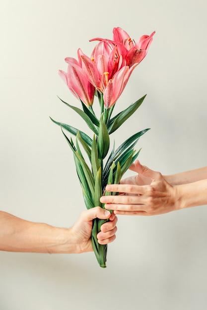 A mão do homem dando buquê de flores de lírios para a mão do woma Foto Premium