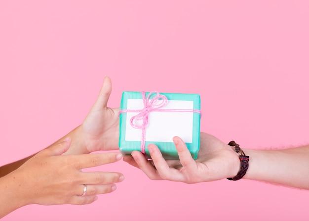 A mão do homem dando caixa de presente para outra pessoa contra um fundo rosa Foto gratuita