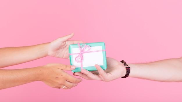 A mão do homem dando de presente para sua mulher contra um fundo rosa Foto gratuita