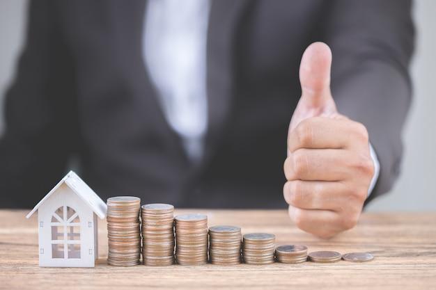 A mão do homem de negócios mostra os polegares acima com dinheiro da pilha da moeda intensifica o crescimento Foto Premium