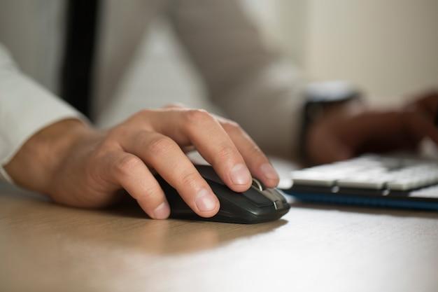 A mão do homem de negócios usa o rato do computador e a datilografia, formulário do acordo da parceria grampeado para almofada o close up. sucesso nos negócios, contrato e documento importante, papelada ou conceito de advogado Foto Premium