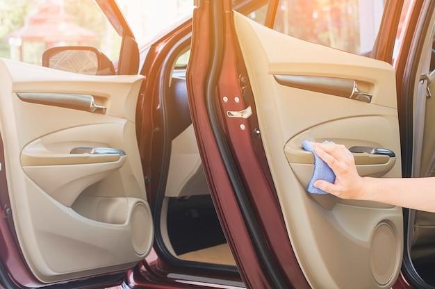 A mão do homem está limpando e encerando o carro Foto gratuita
