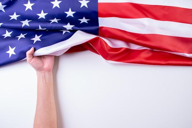 A mão do homem mantém bandeiras americanas contra um fundo branco. Foto Premium