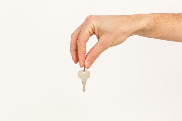 A mão do homem mantém uma chave isolada em um fundo branco Foto Premium