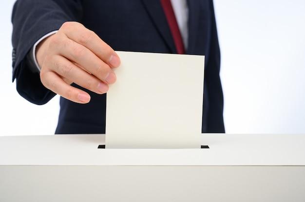 A mão do homem nas urnas nas urnas. Foto Premium