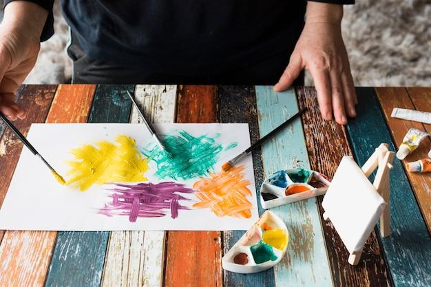 A mão do homem pintar pincelada colorida em papel branco Foto gratuita