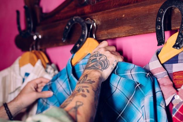 A mão do homem que pendura a camisa xadrez azul no gancho de cabide Foto gratuita