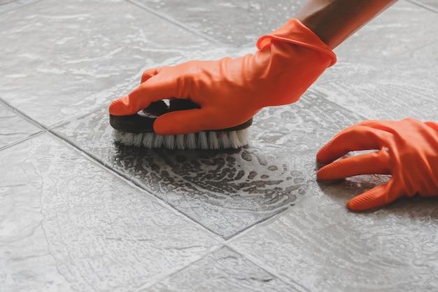 A mão do homem que veste luvas de borracha alaranjadas é usa uma mangueira para limpar o assoalho de telha. Foto Premium