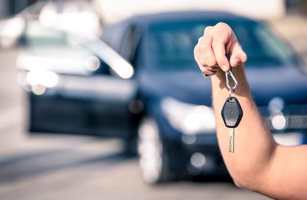 A mão do homem segurando as chaves do carro moderno prontos para locação Foto Premium