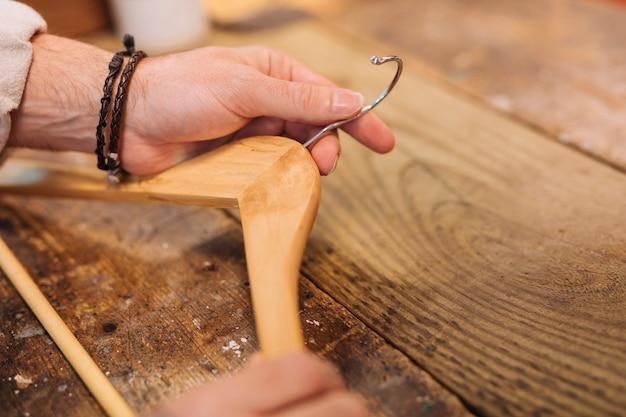 A mão do homem segurando o cabide de madeira na mesa de madeira na loja de roupas Foto gratuita