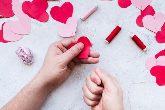 A mão do homem, tornando a festão de forma de coração de papel vermelho e rosa com rosca em fundo branco Foto gratuita