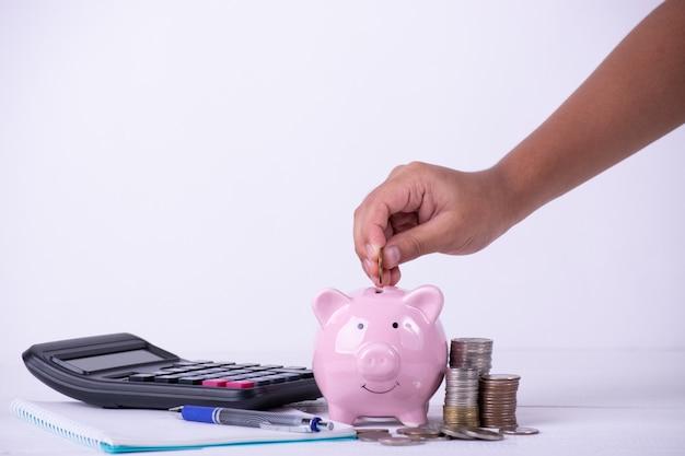 A mão do menino pôs moedas ao mealheiro, pilha de moedas, cálculos, conceito do dinheiro das economias. Foto Premium