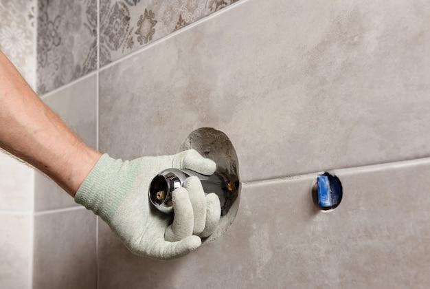 A mão do trabalhador está montando uma torneira embutida Foto Premium
