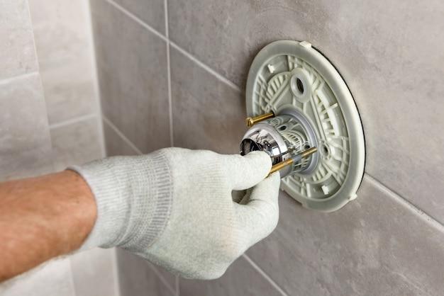 A mão do trabalhador está montando uma torneira embutida. Foto Premium