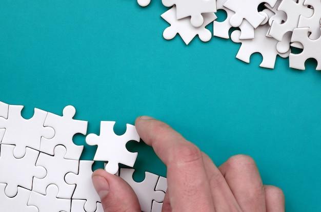A mão dobra um quebra-cabeça branca e uma pilha de peças de quebra-cabeça desarrumada encontra-se Foto Premium