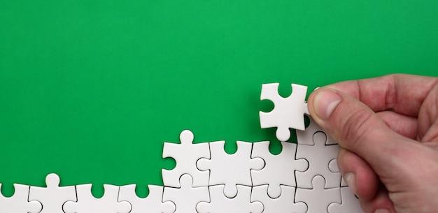 A mão dobra um quebra-cabeça branca no contexto da superfície verde Foto Premium