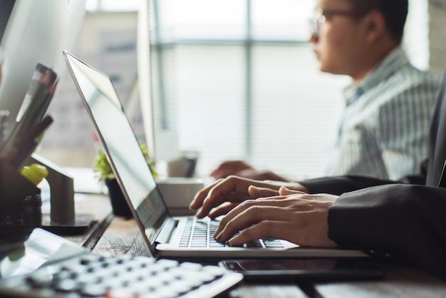 A mão dos empregados está trabalhando no escritório. seu computador está digitando dados financeiros. Foto Premium
