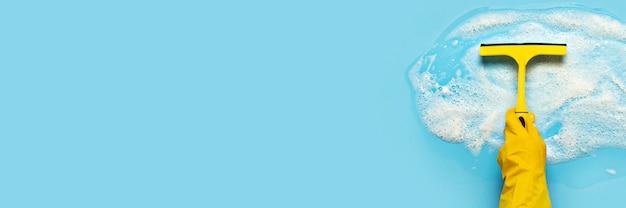 A mão em uma luva de borracha amarela segura um raspador para limpar e limpa a espuma de sabão sobre uma superfície azul. conceito de limpeza, serviço de limpeza. . vista plana, vista superior Foto Premium