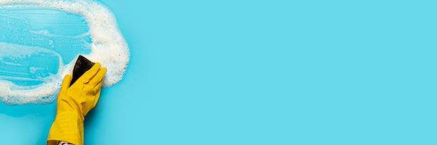 A mão em uma luva de borracha amarela segura uma esponja de limpeza e limpa uma espuma com sabão sobre uma superfície azul. conceito de limpeza, serviço de limpeza. . vista plana, vista superior Foto Premium