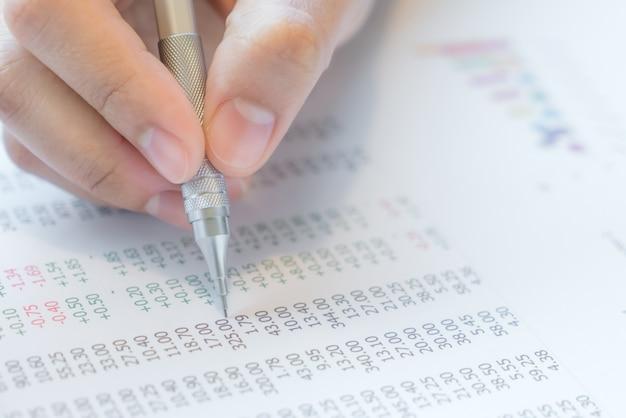 A mão escreve em várias cartas financeiras na tabela Foto gratuita