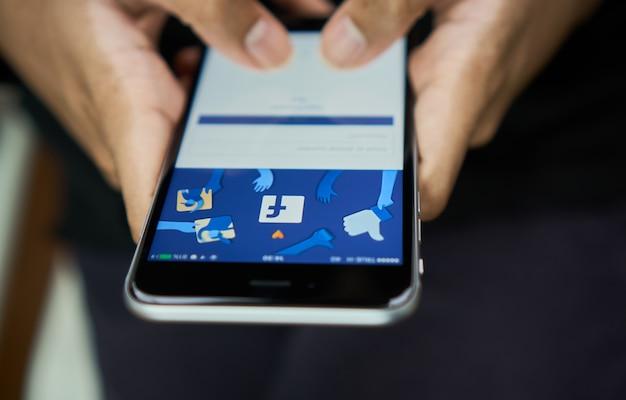 A mão está pressionando a tela do facebook Foto Premium