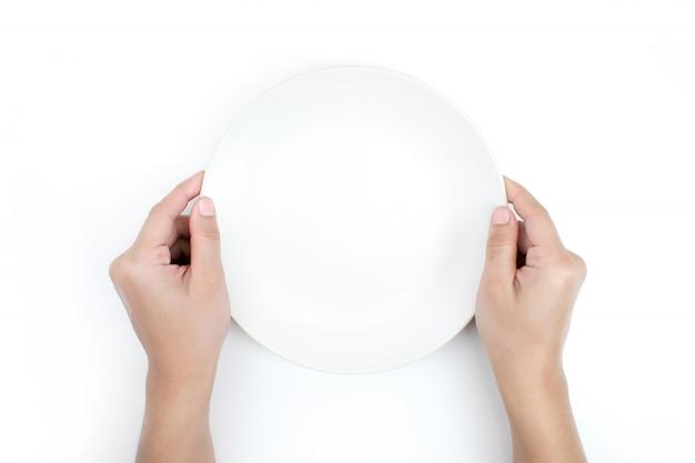 A mão está segurando o prato na vista superior. isolado fundo branco. Foto Premium