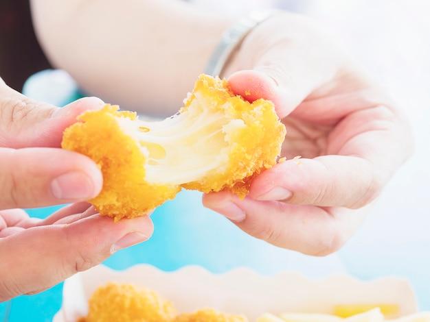 A mão está segurando uma bola de queijo stretch pronto para ser comido sobre o fundo azul da tabela Foto gratuita