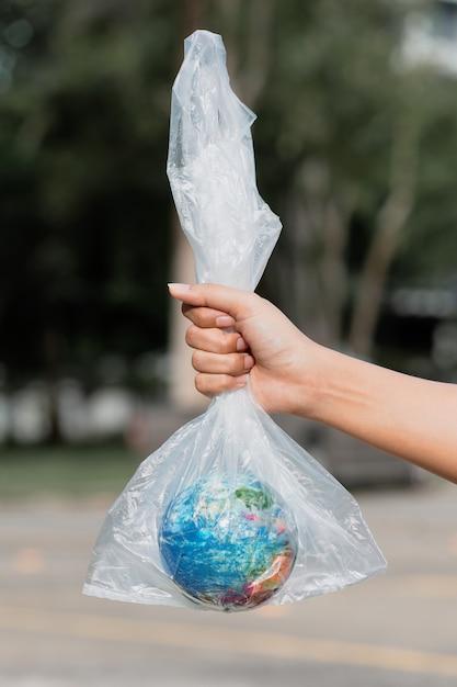 A mão humana segura o planeta terra em um saco plástico. o conceito de poluição por detritos plásticos. aquecimento global devido ao efeito estufa Foto Premium