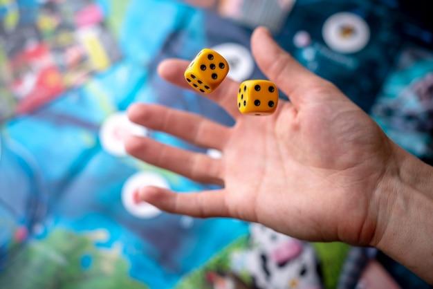 A mão lança dois dados amarelos no campo de jogo. o conceito de jogos de tabuleiro. momentos de jogo na dinâmica Foto Premium
