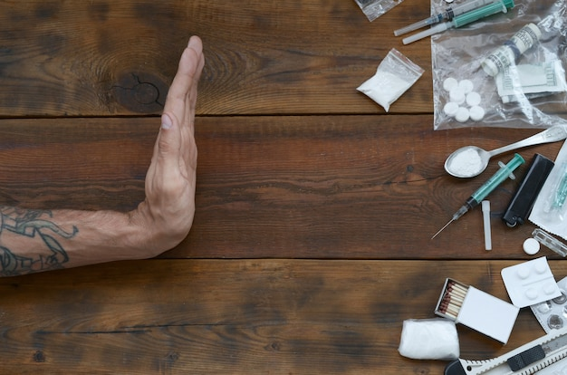 A mão masculina mostra o sinal de stop para todas as definições de material narcótico. muitos comprimidos de drogas e pó na mesa de madeira Foto Premium