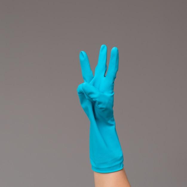 A mão na luva cirúrgica mostra três dedos no fundo neutro. copie o espaço. Foto Premium