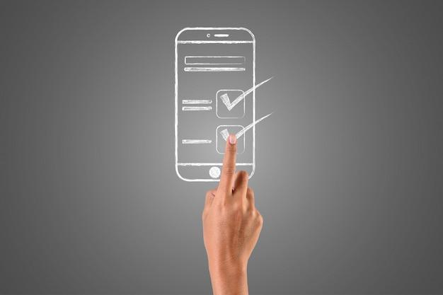 A mão que toca o smartphone é escrita com um giz branco na mão, desenhar o conceito. Foto gratuita