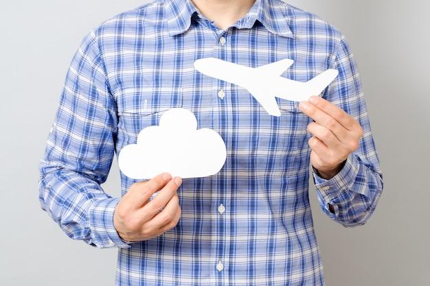 A mão segurando o modelo de papel branco de avião e nuvem Foto Premium