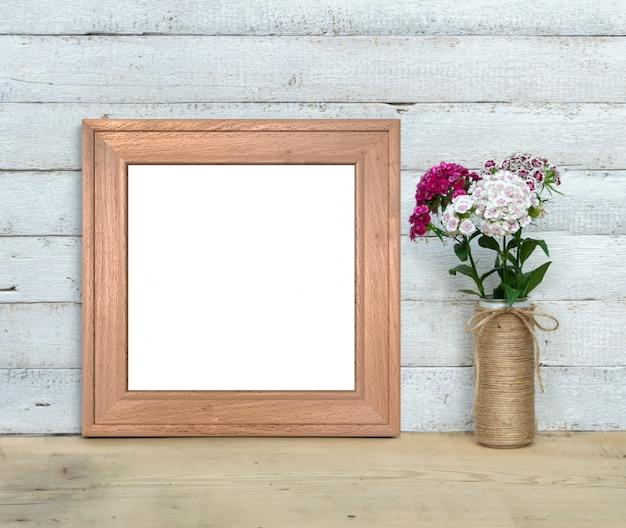 A maquete quadrada do quadro de madeira velho perto de um buquê de william doce fica em uma mesa de madeira em um fundo de madeira branco pintado. estilo rústico, beleza simples. 3d rendem. Foto Premium