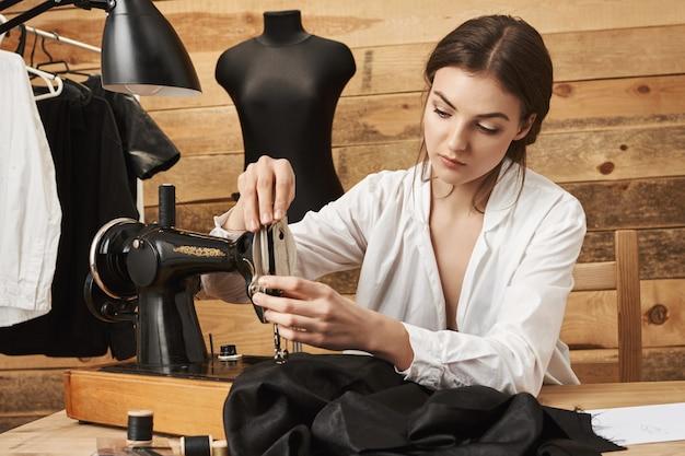 A máquina de costura deve ser tratada adequadamente. a designer feminina focada costurou as roupas na oficina, colocando a linha no soquete, tentando terminar a roupa a tempo de entregá-la ao cliente. o equipamento ficará ótimo Foto gratuita