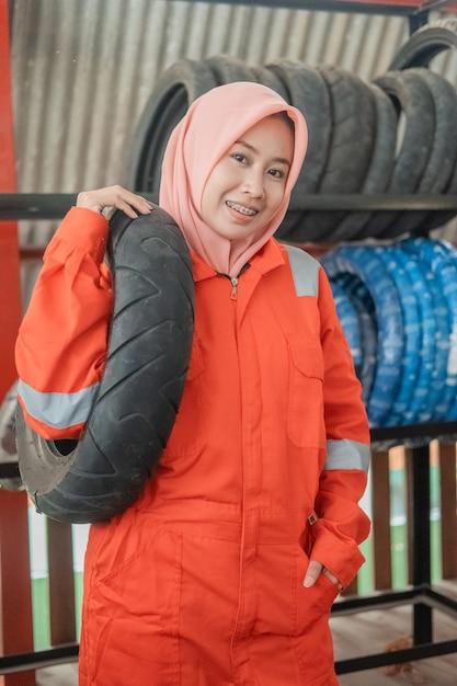 A mecânica com véu usa um uniforme do wearpack ao carregar um pneu de motocicleta enquanto está em uma oficina mecânica Foto Premium