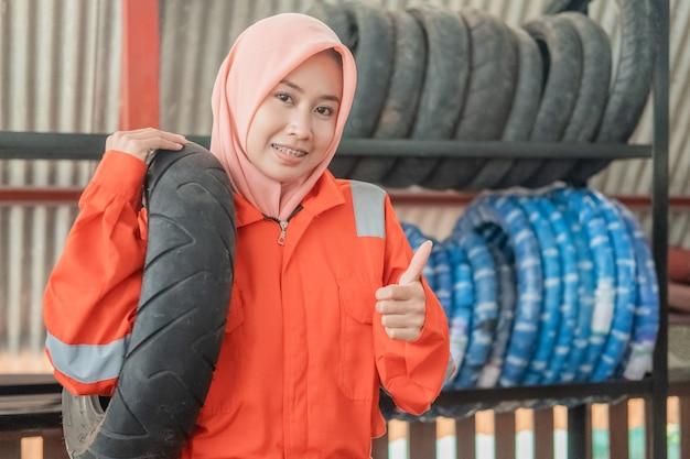 A mecânica com véu usa um uniforme do wearpack com um polegar para cima ao carregar um pneu de motocicleta enquanto está em uma oficina mecânica Foto Premium