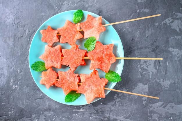 A melancia sob a forma das estrelas em espetos com as folhas da hortelã encontra-se em uma placa. Foto Premium