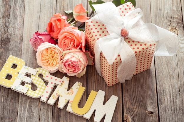A melhor mãe escrita em letras de madeira multicoloridas, rosa presente e fresca. feliz dia das mães Foto Premium