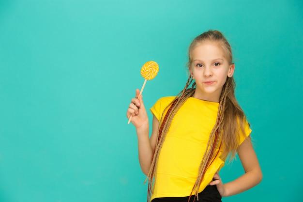 A menina adolescente com pirulito colorido em um azul Foto gratuita