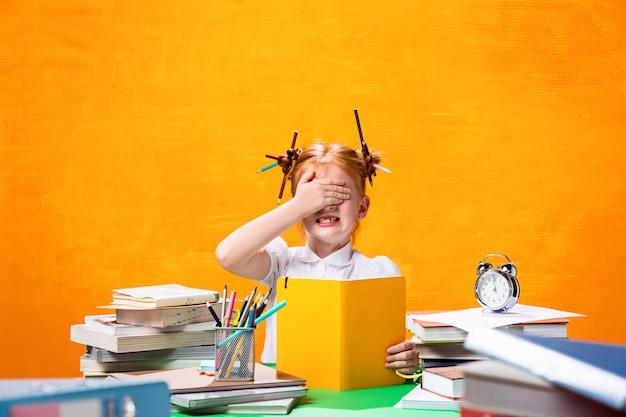 A menina adolescente ruiva com muitos livros em casa. fotografia de estúdio Foto gratuita