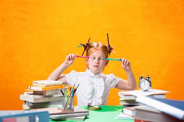 A menina adolescente ruiva com muitos livros em casa. Foto gratuita