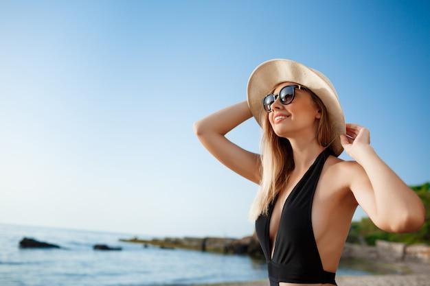 A menina alegre nova bonita no chapéu e nos óculos de sol descansa na praia da manhã Foto gratuita