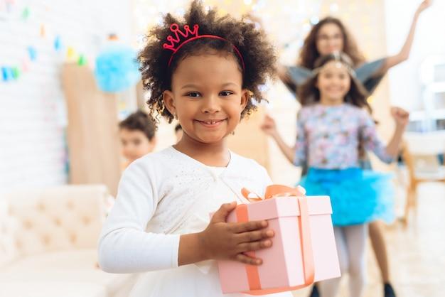 A menina alegre prende o presente na caixa cor-de-rosa na festa de anos. Foto Premium