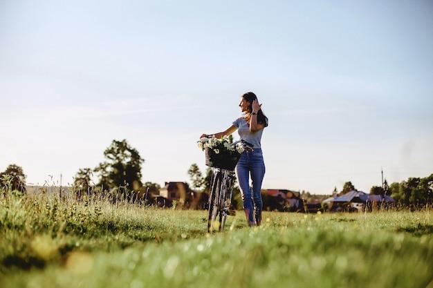 A menina anda com um cachorrinho em um campo em uma bicicleta na parte de trás da luz do sol Foto Premium