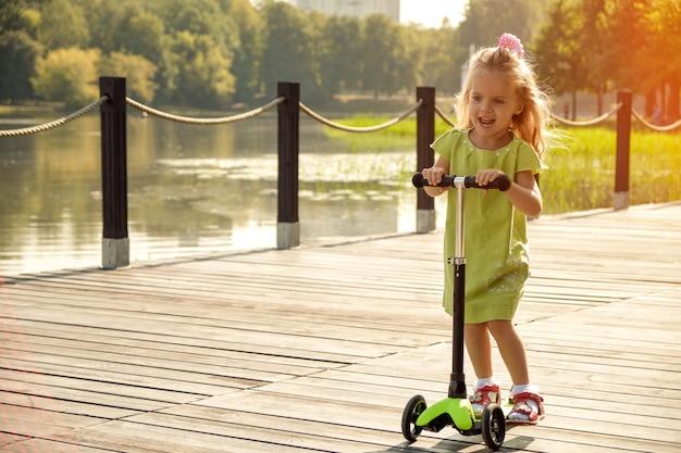 A menina anda de scooter no parque perto da água. criança feliz, entretenimento infantil, criança ativa. Foto Premium